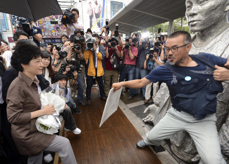In this Tuesday, Aug. 28, 2012 photo, South Korean presidential candidate Park Geun-hye, left, tries to lay flowers in front of Chun Tae-il's statue as Kim Jung-woo, right, a leader of the Ssangyong Motor labor union, blocks her, in Seoul, South Korea. Chun's 1970 labor protest suicide is seen as an expression of dissent against the rule of Park's father, the late president and longtime dictator Park Chung-hee. She attempts to become the country's first female president and keep the government in conservative hands in the Dec. 19 election. (AP Photo/Newsis/Suh Jae-hoon) KOREA OUT