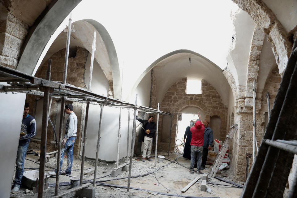 Architects and workers renovate the long-abandoned 200-year-old Ghussein palace, in the old quarter of Gaza City, Monday, Dec. 14, 2020. Less than 200 of these old houses are still partly or entirely standing, according to officials and they are threatened by neglect, decaying and urban sprawl. (AP Photo/Adel Hana)