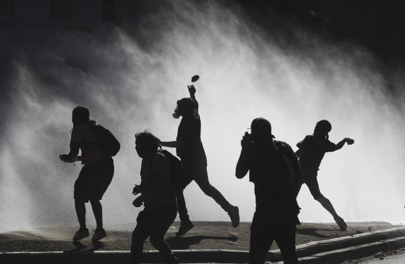 Anti-government demonstrators throw rocks at a police water cannon trying to disperse them in Santiago, Chile, Friday, Dec. 27, 2019. Chile has been roiled by continuing and sometimes violent street protests since Oct. 18, when a student protest over a modest increase in subway fares turned into a much larger and broader movement with a long list of demands that largely focus on inequality. (AP Photo/Fernando Llano)