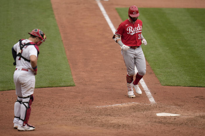 Cincinnati Reds' Jesse Winker, right, arrives home after hitting a solo home run as St. Louis Cardinals catcher Andrew Knizner stands at the plate during the ninth inning of a baseball game Sunday, June 6, 2021, in St. Louis. (AP Photo/Jeff Roberson)
