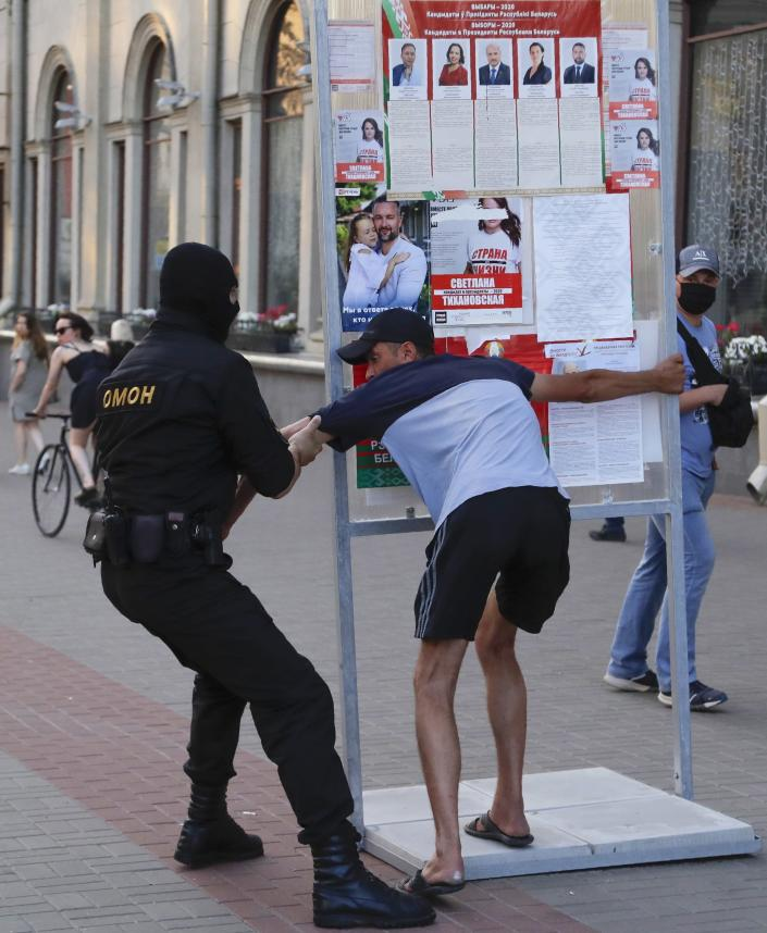 A Belarusian police officer detains a man in Minsk, Belarus, Saturday, Aug. 8, 2020. On Saturday evening, police arrested at least 10 people as hundreds of opposition supporters drove through the center of the capital waving flags and brandishing clenched-fist victory signs from the vehicles' windows. The presidential election in Belarus is scheduled for August 9, 2020. (AP Photo/Sergei Grits)