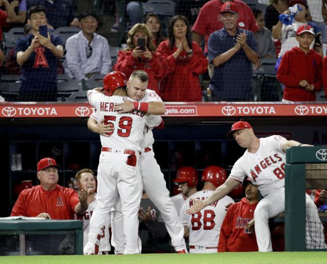 Los Angeles Angels' Michael Hermosillo, left, gets a hug from Mike Trout after his home run against the Texas Rangers during the fourth inning of a baseball game in Anaheim, Calif., Monday, Sept. 24, 2018. (AP Photo/Chris Carlson)