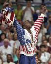"""FILE - In this Aug. 8, 1992, file photo, USA's Earvin """"Magic"""" Johnson rejoices with his gold medal after beating Croatia 117-85 in the gold medal game in men's basketball at the Summer Olympics in Barcelona. (AP Photo/Susan Ragan, File)"""