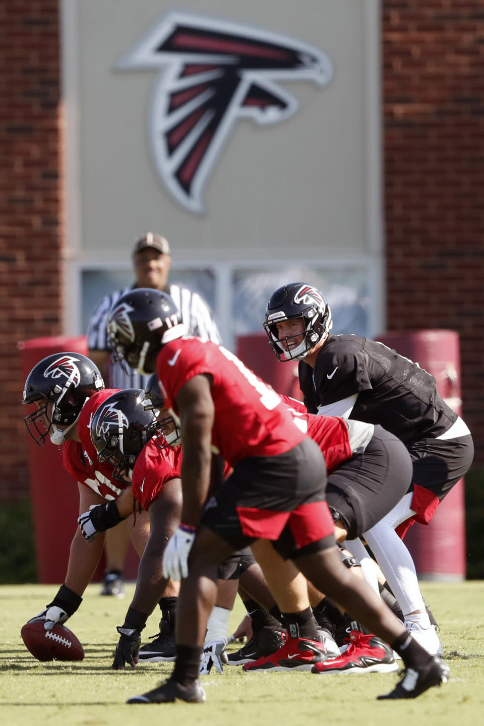 FILE - In this July 25, 2019, file photo, Atlanta Falcons quarterback Matt Ryan (2) and the offense prepare to run a play during their NFL training camp football practice in Flowery Branch, Ga. Several NFL teams are reopening their training facilities Tuesday, May 19, 2020, while many are prohibited by government restrictions during the coronavirus pandemic. Among the teams taking advantage of using their buildings on the first day they are allowed are the Falcons, Cardinals and Colts. (AP Photo/John Bazemore, File)