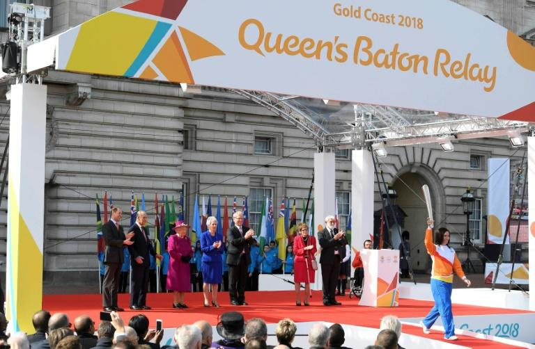 Retired cysclist Anna Meares (R) from Australia carries the baton after receiving it from Britain's Queen Elizabeth during the launch of the Queen's baton relay for the 2018 Commonwealth Games at Buckingham Palace in London on March 13, 2017