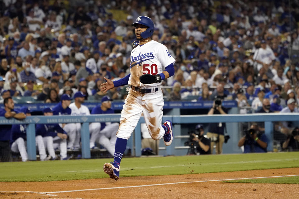Los Angeles Dodgers' Mookie Betts scores on a single from Corey Seager during the first inning of a baseball game against the Arizona Diamondbacks Monday, Sept. 13, 2021, in Los Angeles. (AP Photo/Marcio Jose Sanchez)
