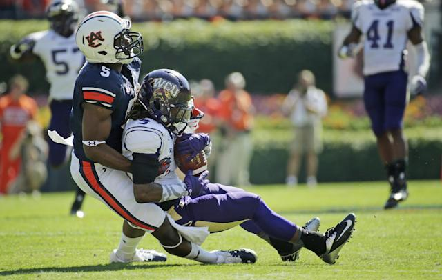 Western Carolina defensive back Fred Payne (3) is taken down after making an interception by Auburn wide receiver Ricardo Louis (5) during the first half of an NCAA college football game in Auburn, Ala., Saturday, Oct. 12, 2013. (AP Photo/Dave Martin)