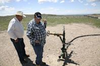 Two workers look at a gas well on the Crow Nation reservation near Crow Agency, Montana, May 30, 2008. REUTERS/Adam Tanner