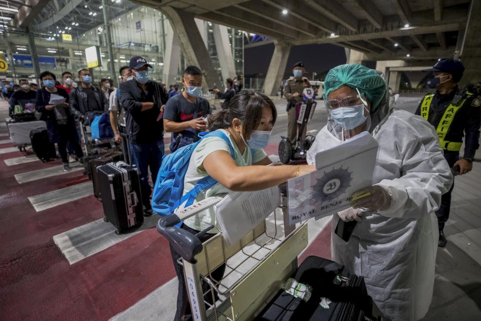 "A public health worker screens Chinese tourists from Shanghai who arrived at Suvarnabhumi airport on a ""Special Tourist Visa, in Bangkok, Thailand, Tuesday, Oct 20, 2020. Thailand on Tuesday took a modest step toward reviving its coronavirus-battered tourist industry by welcoming 39 visitors who flew in from Shanghai, the first such arrival since normal traveler arrivals were banned almost seven months ago. (AP Photo/Wason Wanichakorn)"