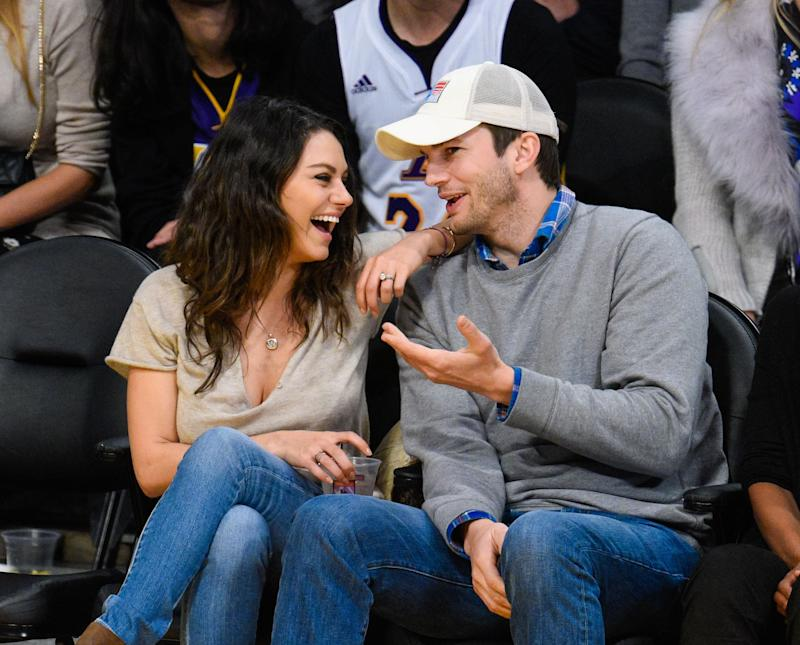 Mila Kunis sits with Ashton Kutcher at a game