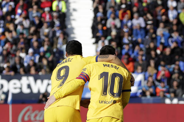 Barcelona's Luis Suarez, left, celebrates with Barcelona's Lionel Messi after scoring his side's opening goal during a Spanish La Liga soccer match between Leganes and FC Barcelona at the Butarque stadium in Madrid, Spain, Saturday Nov. 23, 2019. (AP Photo/Paul White)