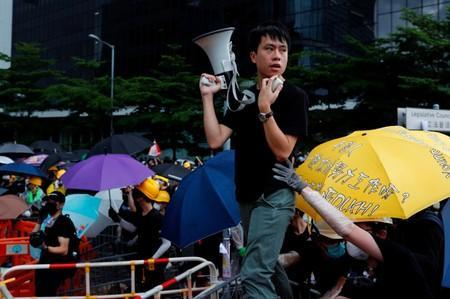 Lawmaker Roy Kwong Chun-yu speaks to anti-extradition bill protesters during a demonstration near a flag raising ceremony for the anniversary of Hong Kong handover to China in Hong Kong