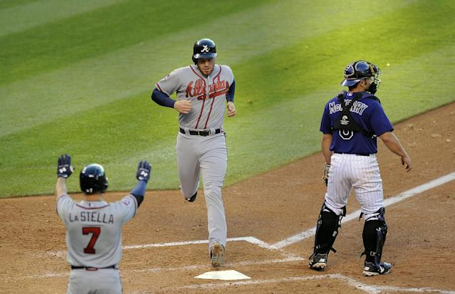 Atlanta Braves Tommy La Stella, left. congratulates Freddie Freeman, center, as he crosses home plate on an RBI single by Chris Johnson as Colorado Rockies catcher Michael McKenry, right, waits for the throw in the fourth inning of a baseball game on Monday, June 9, 2014, in Denver. (AP Photo/Chris Schneider)
