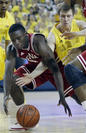 Indiana guard Victor Oladipo, left, and Michigan guard Spike Albrecht chase a loose ball during the first half of an NCAA college basketball game Sunday, March 10, 2013, in Ann Arbor, Mich. (AP Photo/Duane Burleson)