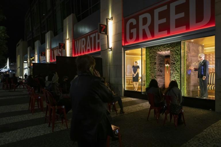 A theater group in Miami Beach has devised a unique way of performing during the pandemic, with actors behind storefront windows and the audience watching from outside