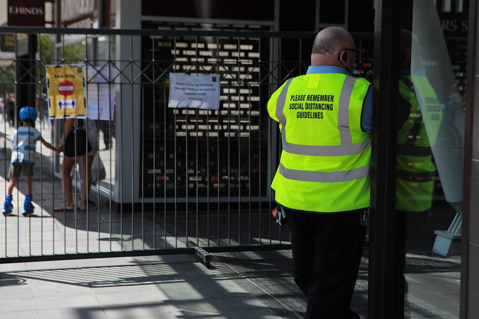 A security guard has a social distancing message on his vest as lockdown restrictions have been relaxed to allow non-essential shops to reopen in England