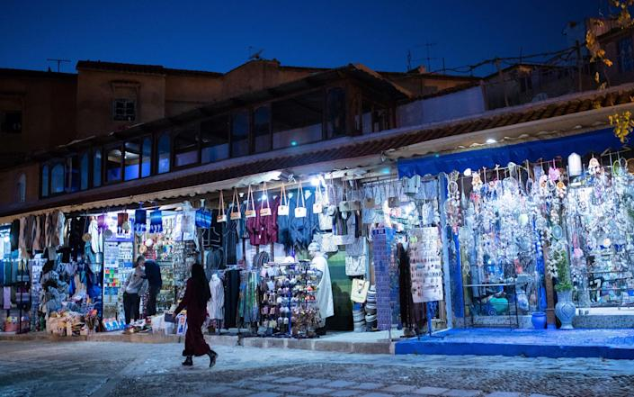 Shop owners selling souvenirs wait for customers in an alleyway in Chefchaouen - AP