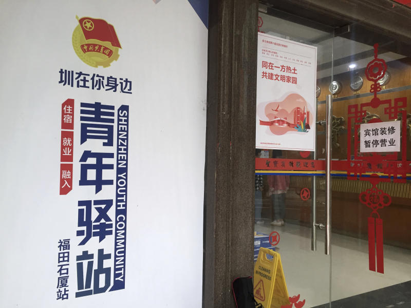 """In this Thursday, Nov. 14, 2019 photo, the flag of China's Communist Youth League is seen on a sign at the entrance of a youth hostel that is offering free temporary lodging to mainland Chinese students enrolled in Hong Kong Schools in Shenzhen in southern China's Guangdong Province. Since anti-government demonstrators in Hong Kong began barricading university campuses earlier this week, hundreds of mainland Chinese students have retreated to neighboring Shenzhen, where the ruling Communist Party's Youth League has promised them a """"warm home."""" (AP Photo/Yanan Wang)"""
