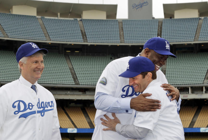 Guggenheim Baseball Management group member Mark Walter, left, smiles, as Magic Johnson, rear center, hugs Peter Guber during a news conference at Dodger Stadium in Los Angeles, Wednesday, May 2, 2012. The franchise's prestige and fan support declined during the stormy ownership tenure of Frank McCourt, who sold the Los Angeles Dodgers for $2 billion to the group fronted by Johnson, headed by Walter and run by Stan Kasten. (AP Photo/Damian Dovarganes)