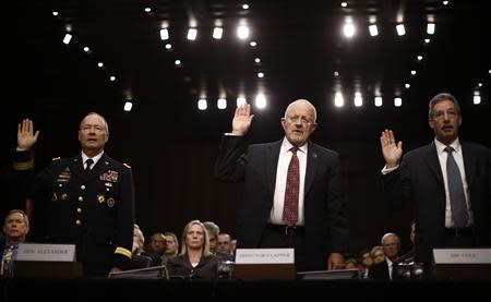 U.S. National Security Agency Director General Keith Alexander (L), Director of National Intelligence James Clapper and Deputy Attorney General James Cole (R) are sworn in to testify at a Senate Intelligence Committee hearing the Foreign Intelligence Surveillance Act legislation on Capitol Hill in Washington, September 26, 2013. REUTERS/Jason Reed