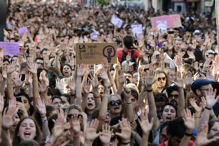 Protesters raise their hands at a rally in Madrid