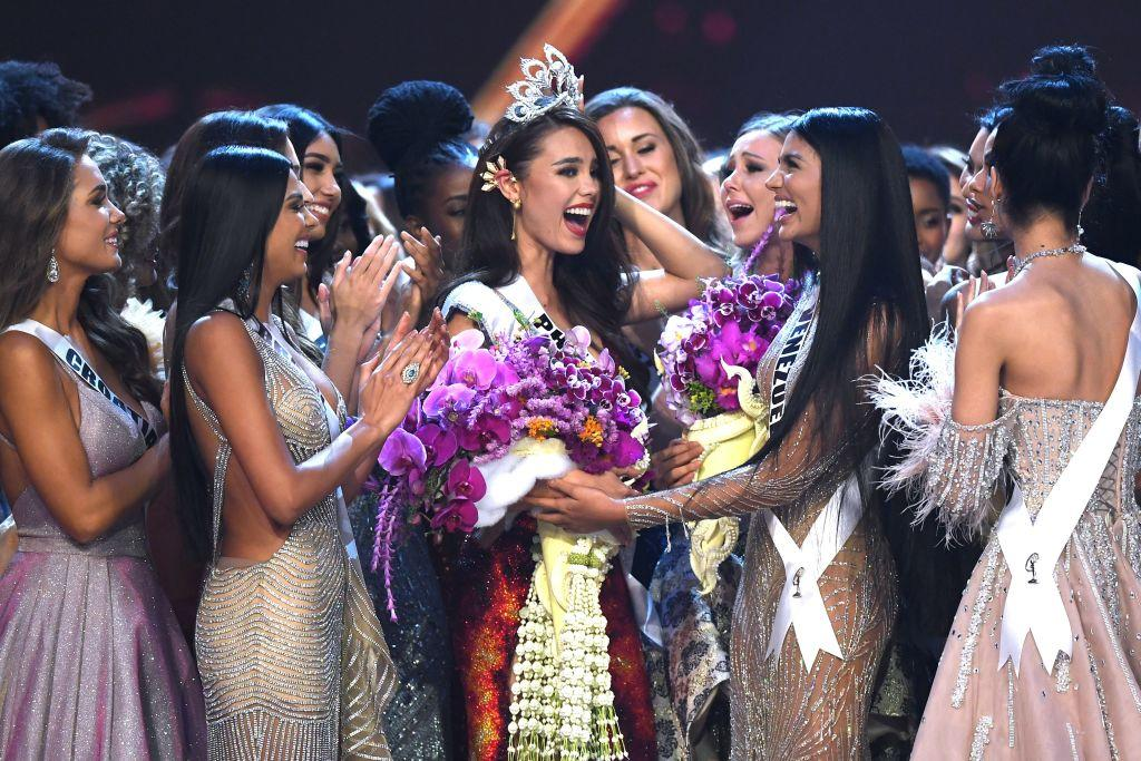 <p>Catriona Gray of the Philippines (C) is congratulated by contestants after winning the Miss Universe 2018 on December 17, 2018 in Bangkok. (Photo credit: LILLIAN SUWANRUMPHA/AFP/Getty Images) </p>