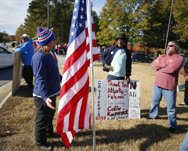 Protesters and supporters wait at the gate to the Atlanta Falcons' training facility where free agent quarterback Colin Kaepernick was set to workout for NFL football scouts, Saturday, Nov. 16, 2019, in Flowery Branch, Ga. The workout was moved to a high school in Riverdale, Ga. (AP Photo/Todd Kirkland)