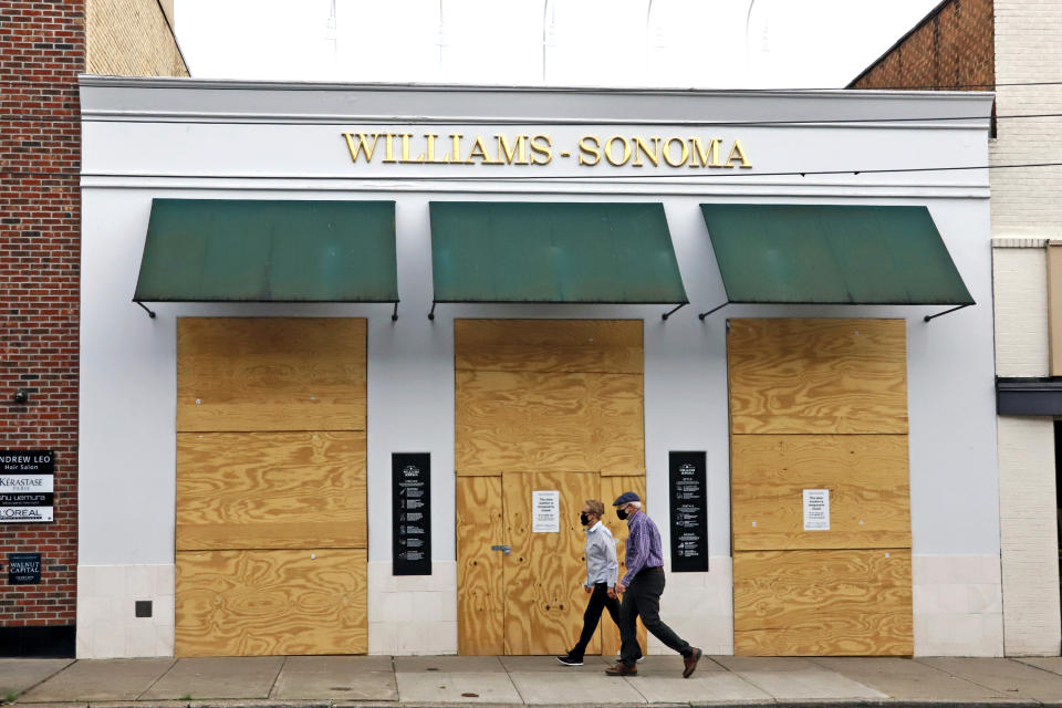 A couple walks in the Shadyside shopping district of Pittsburgh past a Williams-Sonoma store that is boarded up temporarily due to social distancing mandated due to COVID-19 on Wednesday, April 29, 2020. (AP Photo/Gene J. Puskar)