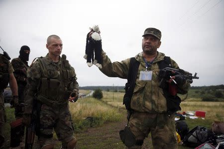 A pro-Russian separatist holds a stuffed toy found at the crash site of Malaysia Airlines flight MH17, near the settlement of Grabovo in the Donetsk region, July 18, 2014. REUTERS/Maxim Zmeyev