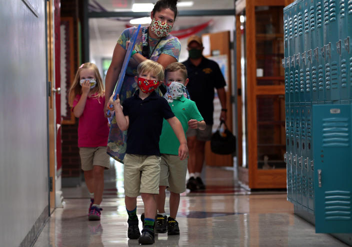 Kindergarten teacher Holly Rupprecht carries plexiglass panels to her room with help from Maelene Wright, left, her brother Hank Wright, and Rupprecht's son Theo at Zion Lutheran School in Bethalto, Ill. on Monday, July 20, 2020. The teacher designed her own table dividers with construction help from her father. (Robert Cohen/St. Louis Post-Dispatch via AP)