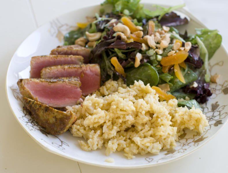 This Nov. 18, 2013 photo shows coconut cashew salad with apricots and seared curry rubbed tuna with mango tahini rice in Concord, N.H. It's a mash-up that draws on the flavors of the Caribbean, Southeast Asia and Europe. (AP Photo/Matthew Mead)