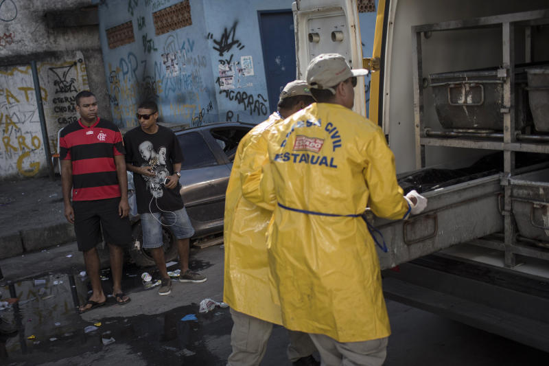 Residents watch as workers remove the body of a man killed during a police operation in the Nova Holanda slum, part of the Complexo da Mare, in Rio de Janeiro, Tuesday, June 25, 2013. The police operation aimed to capture an alleged looter, who according to police killed an officer after a peaceful protest Monday night. At least seven people died and two suspects were captured during Tuesday's operation, according to police. (AP Photo/Felipe Dana)
