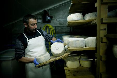 FILE PHOTO: French farmer Cedric Briand inspects cheese that ages in a storage room at a farm in Plesse