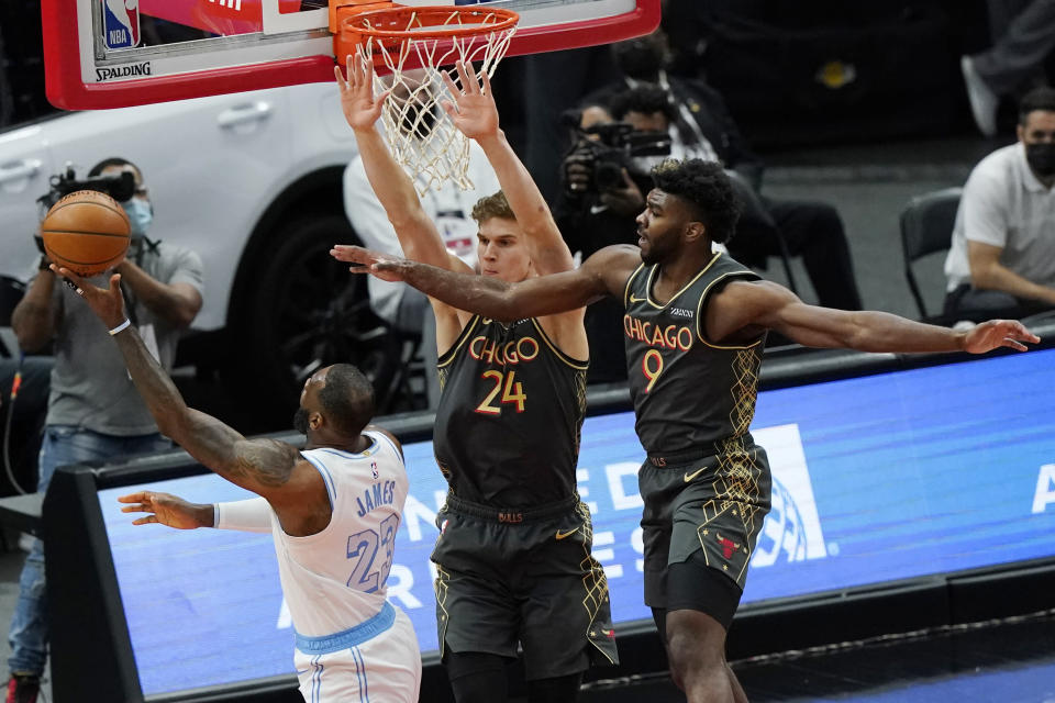 Los Angeles Lakers forward LeBron James, left, shoots against Chicago Bulls forward Lauri Markkanen, center, and forward Patrick Williams during the first half of an NBA basketball game in Chicago, Saturday, Jan. 23, 2021. (AP Photo/Nam Y. Huh)