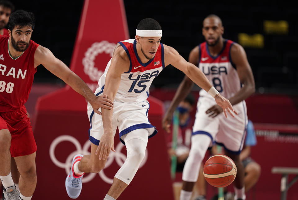 United States' Devin Booker (15), center, steals the ball from Iran's Behnam Yakhchalidehkordi (88), left, during men's basketball preliminary round game at the 2020 Summer Olympics, Wednesday, July 28, 2021, in Saitama, Japan. (AP Photo/Charlie Neibergall)
