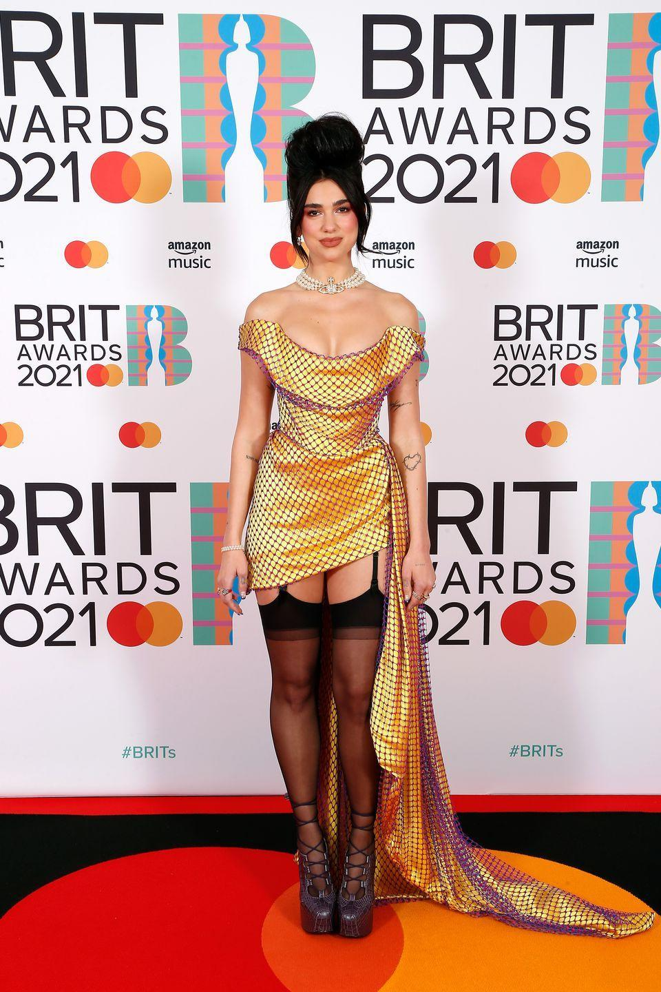 """<p><strong>What: </strong>Vivienne Westwood Couture <strong><br></strong></p><p><strong>Why: </strong>In true Dua Lipa fashion, the singer wore a camp-inspired corseted look on the red carpet from <a href=""""https://www.harpersbazaar.com/celebrity/latest/a36397696/dua-lipa-vivienne-westwood-brit-awards-look/"""" rel=""""nofollow noopener"""" target=""""_blank"""" data-ylk=""""slk:Vivienne Westwood couture"""" class=""""link rapid-noclick-resp"""">Vivienne Westwood couture</a> that was channeling Marie Antoinette in the modern day. Between the stocking garters, platform lace-up booties, and rounded bouffant hairdo to match, Lipa's look was right on the nose.</p>"""