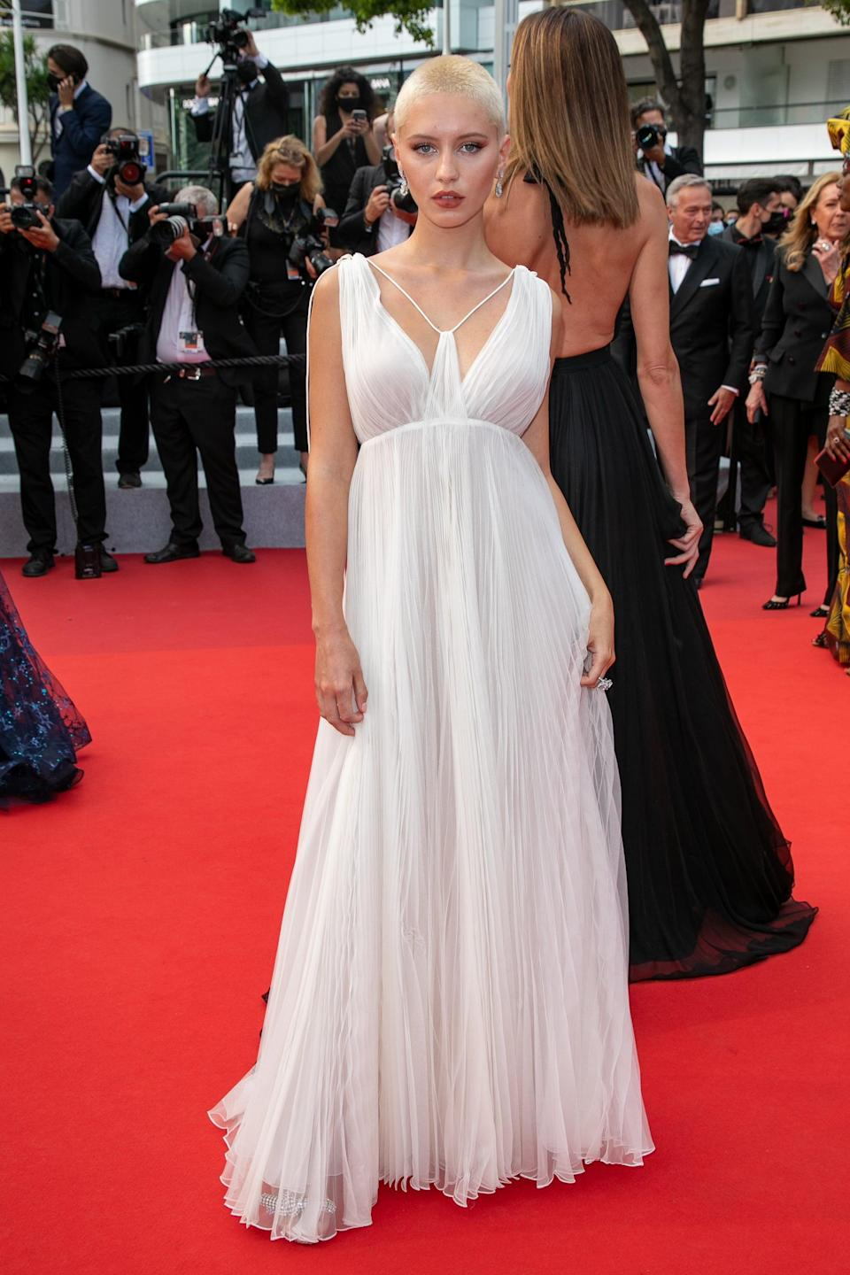 <p>Wearing a white Dior gown.</p>