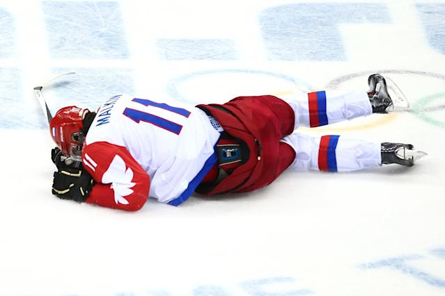 SOCHI, RUSSIA - FEBRUARY 19: Yevgeni Malkin #11 of Russia falls to the ice after colliding with Mikael Granlund #64 of Finland during the Men's Ice Hockey Quarterfinal Playoff on Day 12 of the 2014 Sochi Winter Olympics at Bolshoy Ice Dome on February 19, 2014 in Sochi, Russia. (Photo by Clive Mason/Getty Images)
