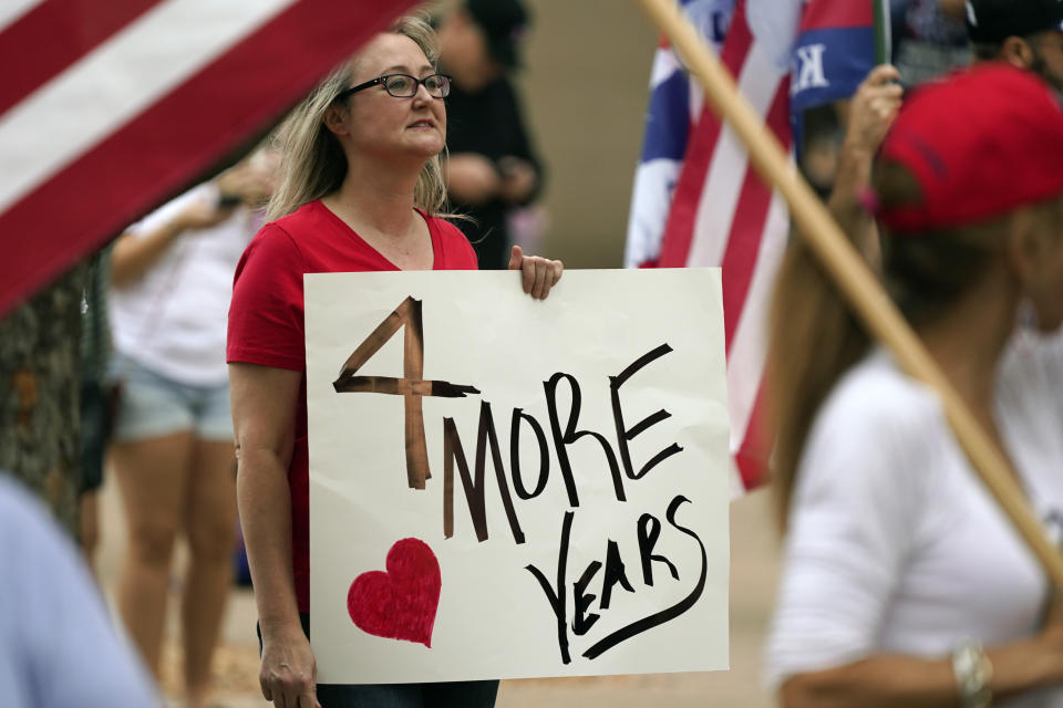 A supporter of President Donald Trump holds a sign during a rally in front of City Hall in Dallas, Saturday, Nov. 14, 2020. (AP Photo/LM Otero)