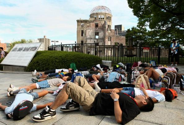 Japanese people stage a die-in protest in front of the Hiroshima Peace Memorial, commonly called the Atomic Bomb Dome at the Hiroshima Peace Memorial Park on August 6, 2012 in Hiroshima. Japan. Tomorrow marks the 67th anniversary of the first atomic bomb that was dropped on Hiroshima by the United States on August 6, 1945, killing an estimated 70,000 people instantly with many thousands more dying over the following years from the effects of radiation. Three days later another atomic bomb was dropped on Nagasaki, ending World War II. (Photo by Buddhika Weerasinghe/Getty Images)