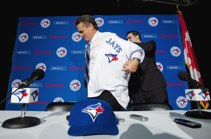 Toronto Blue Jays General Manager Alex Anthopoulos, right, helps new Blue Jays manager John Gibbons, put on his jersey before speaking to he media during a press conference in Toronto on Tuesday, Nov. 20, 2012. (AP Photo/The Canadian Press, Nathan Denette)