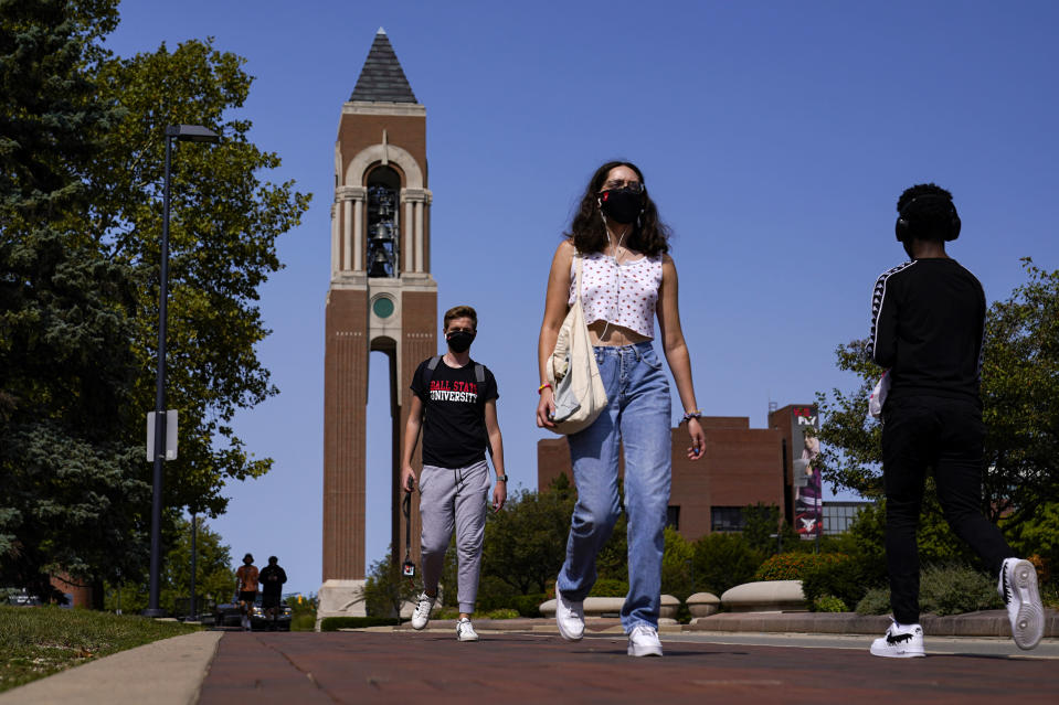 FILE - Masked students walk through the campus of Ball State University in Muncie, Ind., Thursday, Sept. 10, 2020. Colleges across the country are struggling to salvage the fall semester as campus coronavirus cases skyrocket and tensions with local health leaders flare. Schools have locked down dorms, imposed mask mandates, barred student fans from football games and toggled between online and in-person classes. (AP Photo/Michael Conroy)