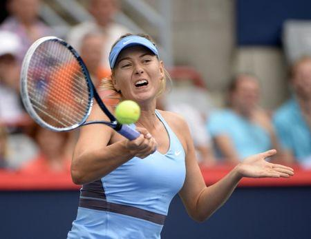 Aug 7, 2014; Montreal, Quebec, Canada; Maria Sharapova (RUS) hits a forehand against Carla Suarez Navarro (ESP) on day four of the Rogers Cup tennis tournament at Uniprix Stadium. Mandatory Credit: Eric Bolte-USA TODAY Sports