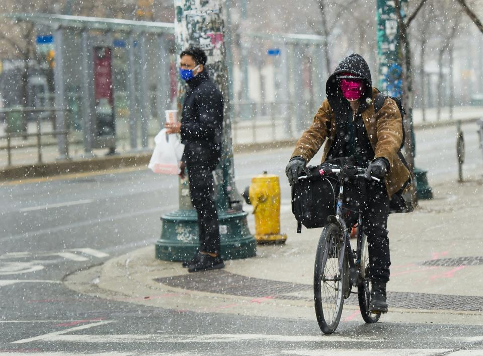 """<span class=""""caption"""">A man cycles in a snow with a mask on in downtown Toronto on April 16, 2020.</span> <span class=""""attribution""""><span class=""""source"""">THE CANADIAN PRESS/Nathan Denette</span></span>"""