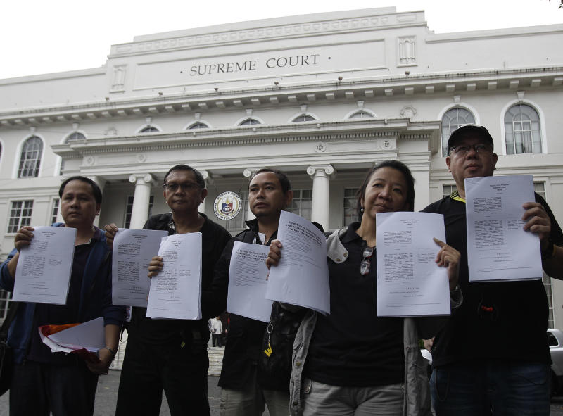 Filipino journalists and some media group leaders hold their petitions against the Cybercrime Prevention Act as they submitted them to the Supreme Court in Manila, Philippines, Wednesday Oct. 3, 2012. Media groups and Filipinos stepped up calls Wednesday for repealing a tough new law that targets cybercrime but activists fear will be used to suppress online freedoms in the Southeast Asian nation. (AP Photo/Aaron Favila)