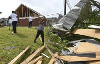 Derrick Pounds Jr. helps his father clean up debris around their house on Elvis Presley Drive in Tupelo, Miss., Monday, May 3, 2021. Multiple tornadoes were reported across the state on Sunday. (AP Photo/Thomas Graning)