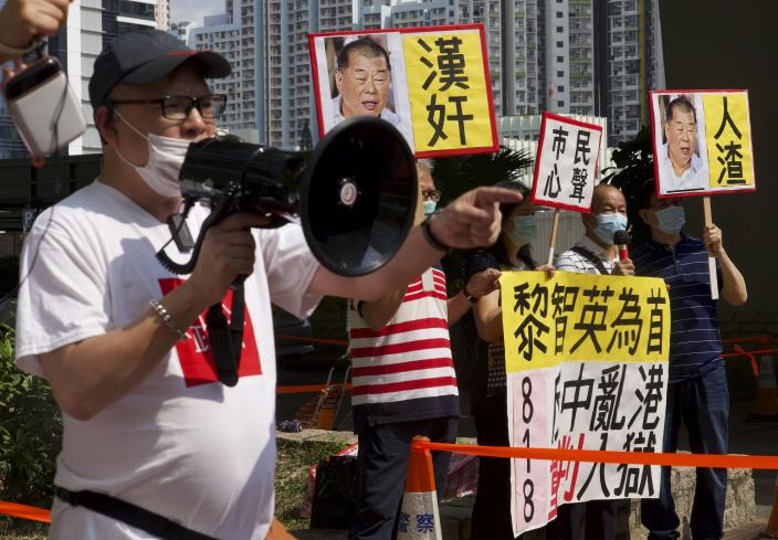 """A pro-China supporter shouts slogans outside a court in Hong Kong Thursday, April 1, 2021. Seven pro-democracy advocates, including media tycoon Jimmy Lai and veteran of the city's democracy movement Martin Lee, are expected to be handed a verdict for organizing and participating in an illegal assembly during massive anti-government protests in 2019 as Hong Kong continues its crackdown on dissent. A sign next to Lai's photo, center, reads """"Traitor."""" (AP Photo/Vincent Yu)"""