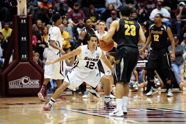 Southern Illinois' Marcus Fillyaw (12) defends Wichita State's Fred VanVleet (23) during the second period of a Missouri Valley Conference NCAA college basketball game in Carbondale, Ill., Thursday, Jan. 2, 2014. Wichita State defeated Southern Illinois 82-67. (AP Photo/Stephen Lance Dennee)
