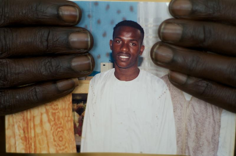 FILE - In this Feb. 5, 2010 file photo, shopkeeper Ousmane Diallo displays a photo of his son Madieye Diallo, a gay activist whose body was disinterred and desecrated hours after burial, in Thies, Senegal. The U.S. embassy in Abidjan made history in June 2013 by hosting a gay pride reception attended by about two dozen openly gay Ivorians. Despite the groundbreaking nature of the event, reporters were barred from attending, and the only mention of it was a short blurb on the embassy website posted the following week. The discreet handling of the event encapsulates the Obama administration's cautious promotion of gay rights in Africa, an issue that is likely to come up during his visit beginning June 26, 2013 to three African nations, two of which punish homosexuality with jail time. (AP Photo/Ricci Shryock, File)