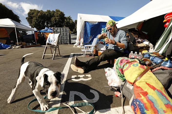 A man and a dog sit outside a tent